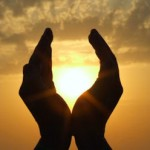 hands holding the sun at dawn